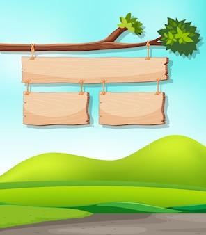 Placas de madeira no galho com fundo da natureza