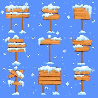 Placas de sinalização nevadas. placa de sinalização de madeira marrom em branco, setas de direção de rua com pingentes no monte de neve, molduras de natal vazias com cobertura de neve e gelo, coleção de inverno isolada de vetor de desenhos animados plana
