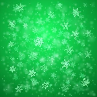 Plano de fundo de natal de complexos flocos de neve caindo e turvos em cores verdes com efeito bokeh