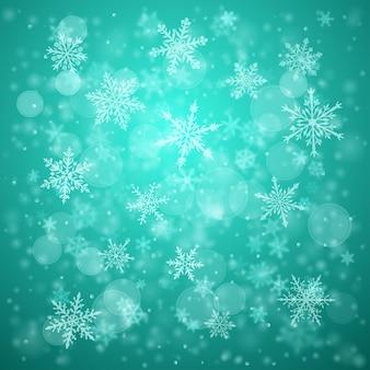 Plano de fundo de natal de complexos flocos de neve caindo nítidos e desfocados em cores turquesas com efeito bokeh