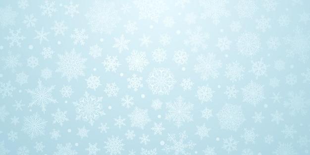 Plano de fundo de natal de flocos de neve complexos grandes e pequenos em cores azuis claras