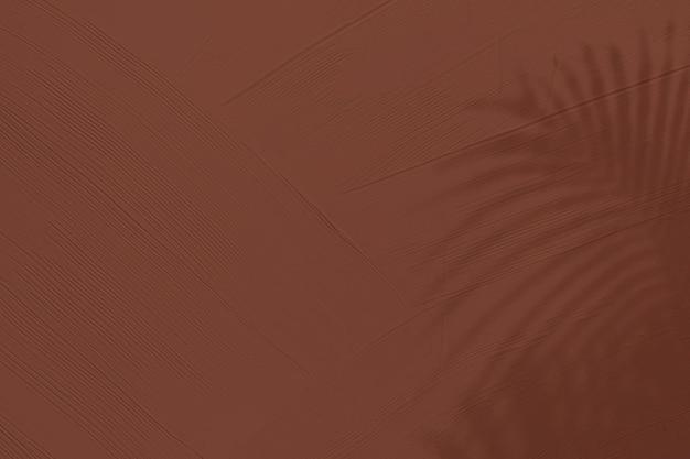 Plano de fundo texturizado marrom com sombra de folha tropical
