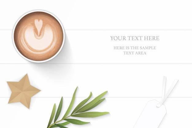 Plano leigo vista superior elegante composição branca café amarelo lápis borracha tag folha de estragão e estrela artesanal no fundo do assoalho de madeira.