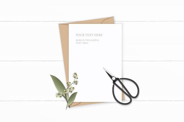 Plano leigo vista superior elegante composição branca carta envelope papel kraft folha de flor e tesoura de metal vintage em fundo de madeira.