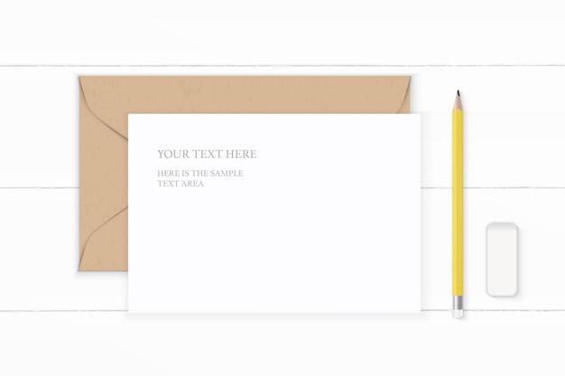 Plano leigo vista superior elegante composição branca carta envelope papel kraft lápis amarelo e borracha no fundo de madeira.