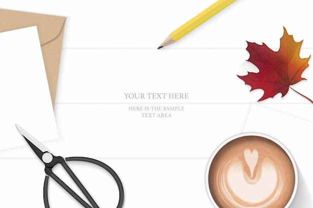 Plano leigo vista superior elegante composição branca carta papel kraft envelope amarelo lápis outono folha de bordo tesouras de metal e café no fundo de madeira.
