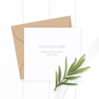 Plano leigo vista superior elegante composição branca carta papel kraft envelope folha de estragão e fita de seda com fundo de madeira.