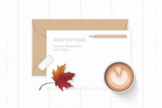 Plano leigo vista superior elegante composição branca carta papel kraft envelope lápis borracha outono folha de plátano e café no fundo de madeira.