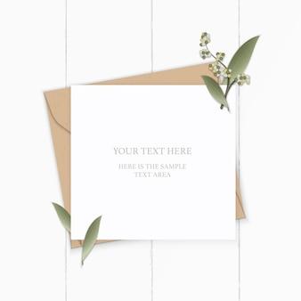 Plano leigo vista superior elegante composição branca carta papel kraft envelope natureza folha flor planta em fundo de madeira.