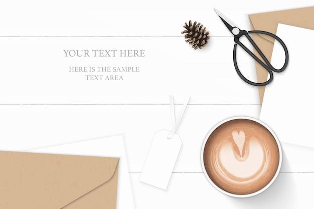 Plano leigo vista superior elegante composição branca letra papel kraft envelope pinho cone etiqueta de café e tesoura de metal vintage em fundo de madeira.