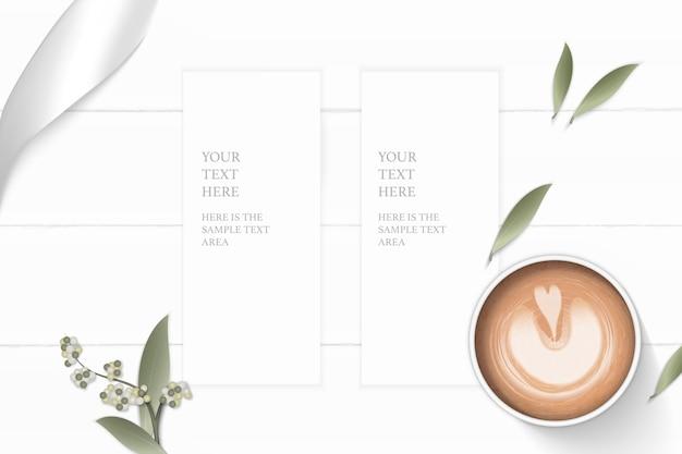 Plano leigo vista superior elegante composição branca papel flor folha café e fita de prata sobre fundo de madeira.