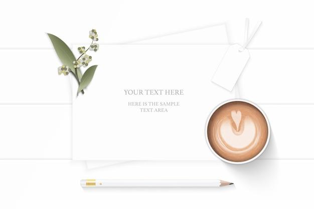 Plano leigo vista superior elegante composição branca papel planta folha flor lápis e café no fundo de madeira.