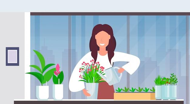 Plantas menina feliz dona de casa feliz mulher cuidar da flor no potenciômetro moderno apartamento home jardinagem interior retrato horizontal