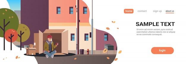 Pobre homem sentado caixa de papelão cara implorando por ajuda mendigo segurando copo de papel cidade desabrigada edifícios de rua cityscape