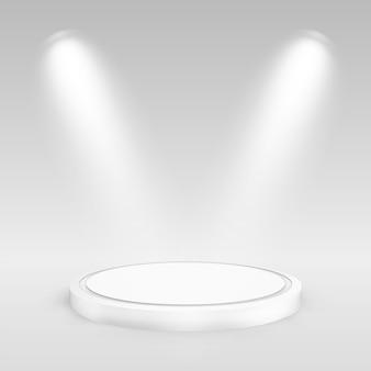 Pódio redondo iluminado por holofotes.