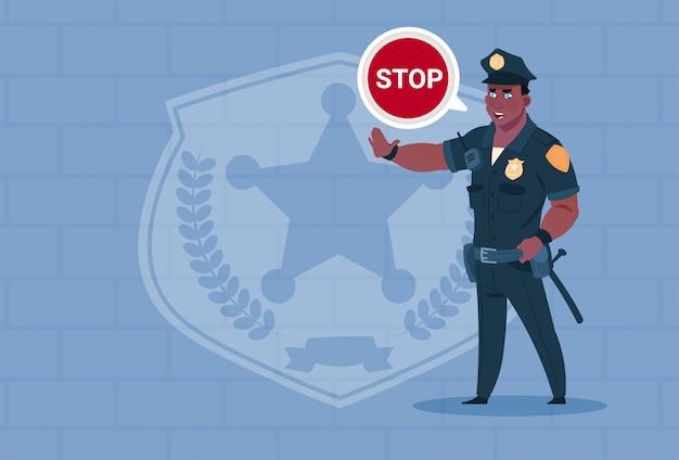 Policial americano africano, com, pare, conversa bolha, desgastar policial uniforme, guarda, sobre, fundo tijolo