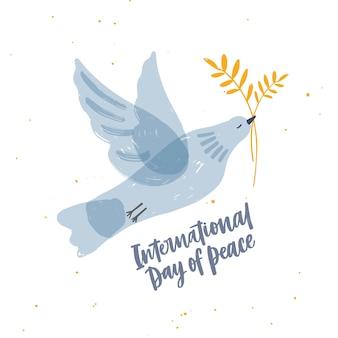 Pomba, pombo ou pássaro translúcido cinza bonito voando e carregando o ramo de oliveira e letras do dia internacional da paz.