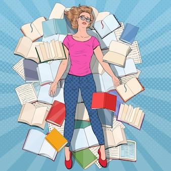 Pop art exausto estudante deitado no chão entre os livros. mulher jovem sobrecarregada, preparando-se para os exames. conceito de educação.