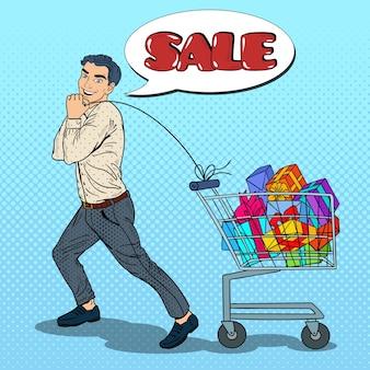 Pop art homem feliz com carrinho de compras cheio de presentes na venda sazonal.