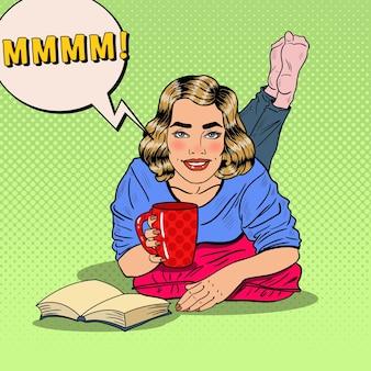 Pop art jovem sorridente mulher bebendo café e lendo um livro. ilustração