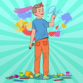 Pop art menino criativo desenho na parede. criança alegre pintura com giz de cera no papel de parede.