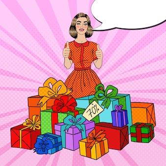 Pop art mulher bonita com caixas de presente enorme e polegares para cima.