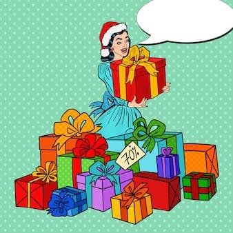 Pop art mulher feliz no chapéu de papai noel com caixas de presente grande na venda de natal.