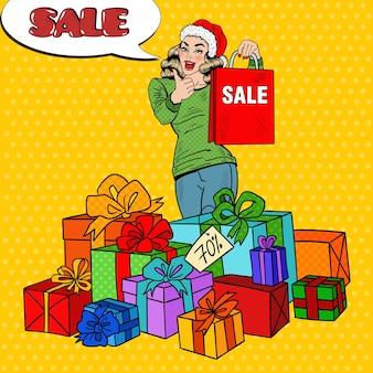 Pop art mulher feliz no chapéu de papai noel com sacola de compras e caixas de presente enorme na venda de natal.