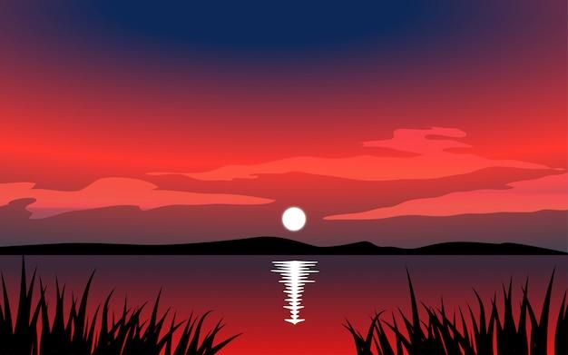 Pôr do sol sobre o lago com silhueta de grama