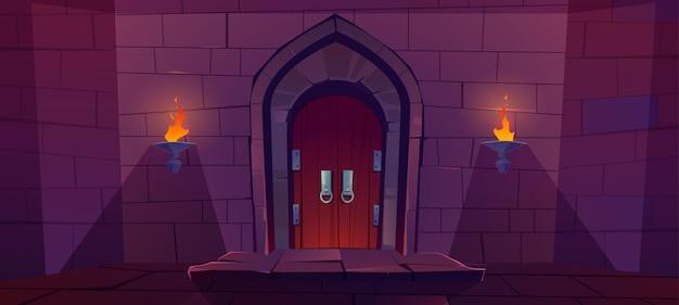 Porta de madeira no castelo medieval. antigo portão no muro de pedra com tochas acesas à noite.