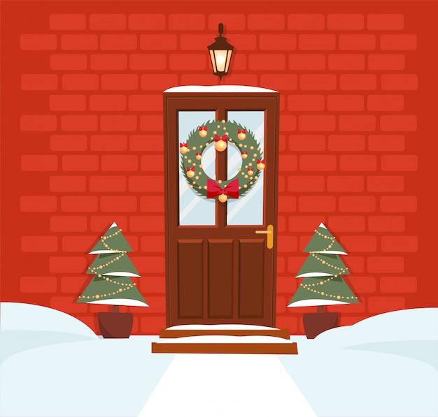 Porta marrom do natal com grinalda, neve e abetos na parede de tijolo vermelho. lanterna forjada acima da porta brilha.