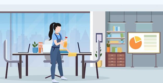Porteiro feminino de uniforme, limpando a mesa de conferência pelo conceito de serviço de limpeza de pano de pó comprimento total interior moderno escritório interior horizontal