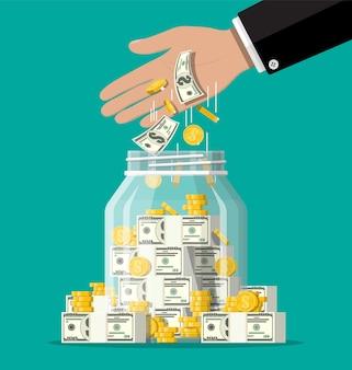Pote de dinheiro de vidro cheio de moedas e notas de ouro