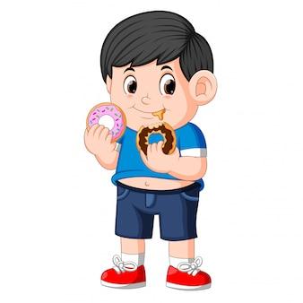Pouco feliz menino bonito está comendo dois donut