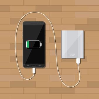 Powerbank cobrando smartphone na mesa de madeira