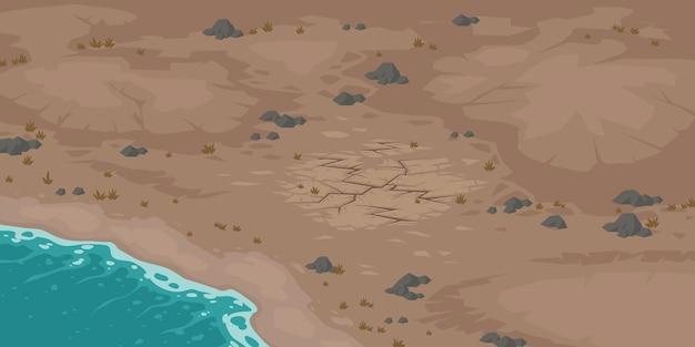 Praia e terreno baldio com solo seco e rachado.