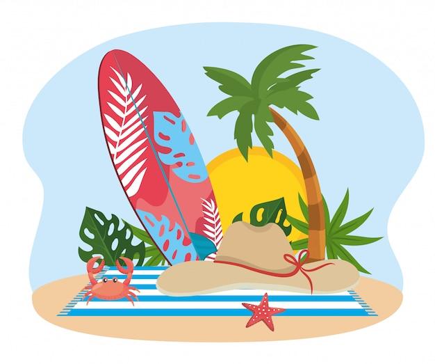 Prancha de surf com palmeira e chapéu com caranguejo na toalha