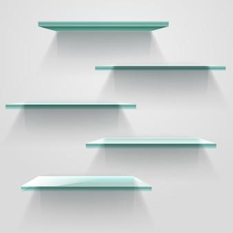Prateleiras vazias de vidro na parede branca.