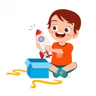Presente aberto feliz do menino pequeno bonito da criança do aniversário
