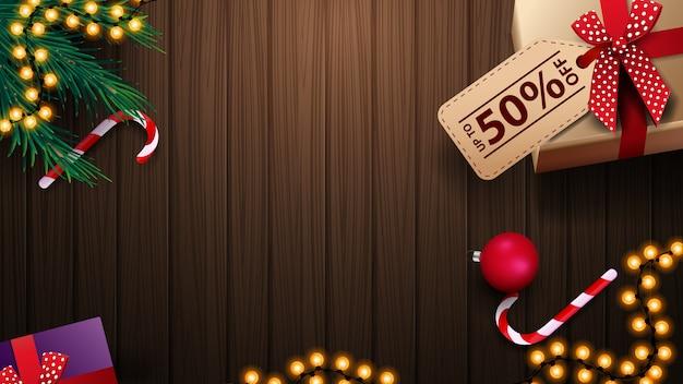 Presente com preço de etiqueta, pirulito, galho de árvore de natal, bola de natal e guirlanda na mesa de madeira, vista superior. fundo para banners de desconto