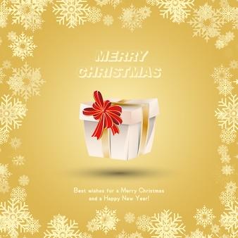 Presente embrulhado com fitas douradas e um laço vermelho contra a neve. cartão festivo de natal e ano novo