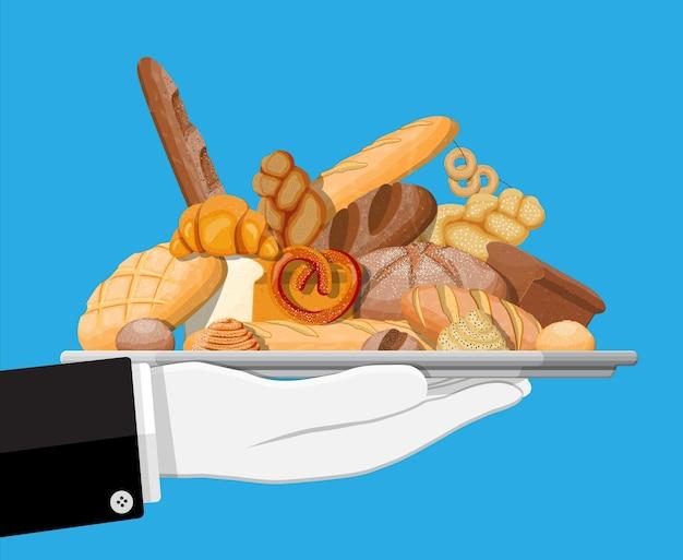Produtos de pão na bandeja na mão. pão integral, de trigo e de centeio, torradas, pretzel, ciabatta, croissant, bagel, baguete francesa, pão de canela. ilustração vetorial em estilo simples