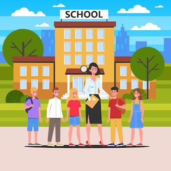Professor e aluno juntos em frente à escola