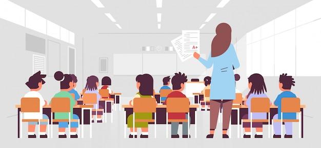 Professora segurando testes com bom um grupo de alunos de vista traseira da classe que senta-se na sala de aula durante a lição que ensina o conceito da educação interior moderno da sala de aula