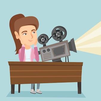 Projecionista caucasiana jovem mostrando um novo filme.