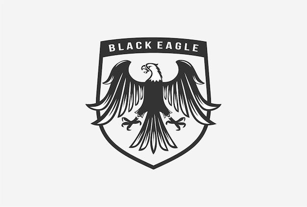 Projeto do logotipo do emblema da águia negra com elemento de escudo.