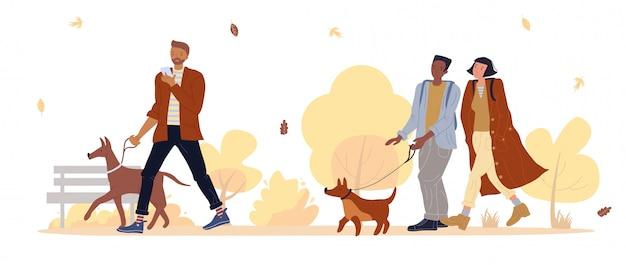 Proprietário do animal de estimação passear com cachorro no parque outono sob queda de folhas