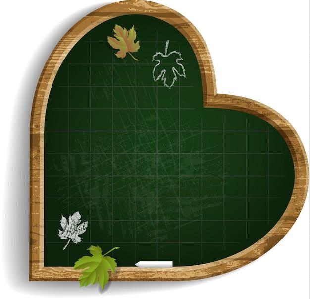 Quadro-negro de forma de coração, giz e folhas.