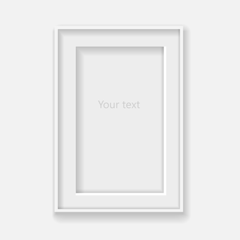 Quadro vertical branco na parede cinza com sombras.