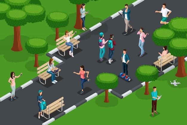 Qualidade isométrica, o conceito de recreação e entretenimento de jovens no parque, com laptops com tablets dos aparelhos modernos de telefone